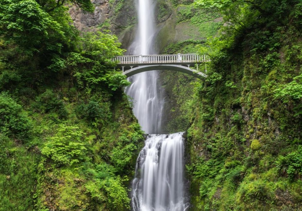 waterfall down green valley with bridge across