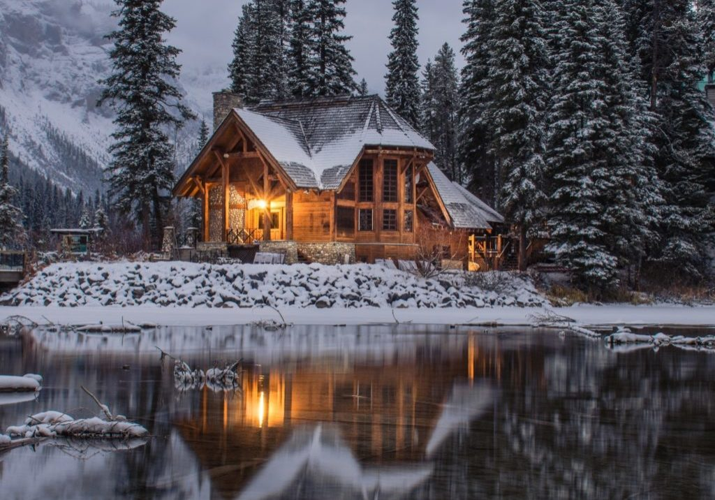 winter wooden cabin light within on a snow lakeshore
