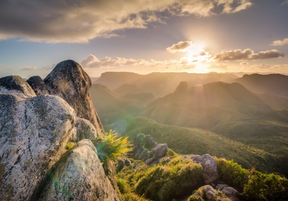 boulders against sunrise and mountain greenspace